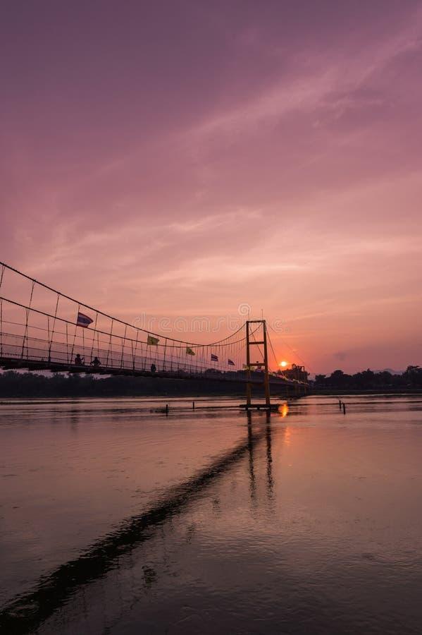 Puente y puesta del sol de la historia de Taksin imagenes de archivo
