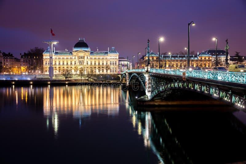 Puente y universidad famosos a lo largo del río Rhone en la noche, Lyon fotos de archivo
