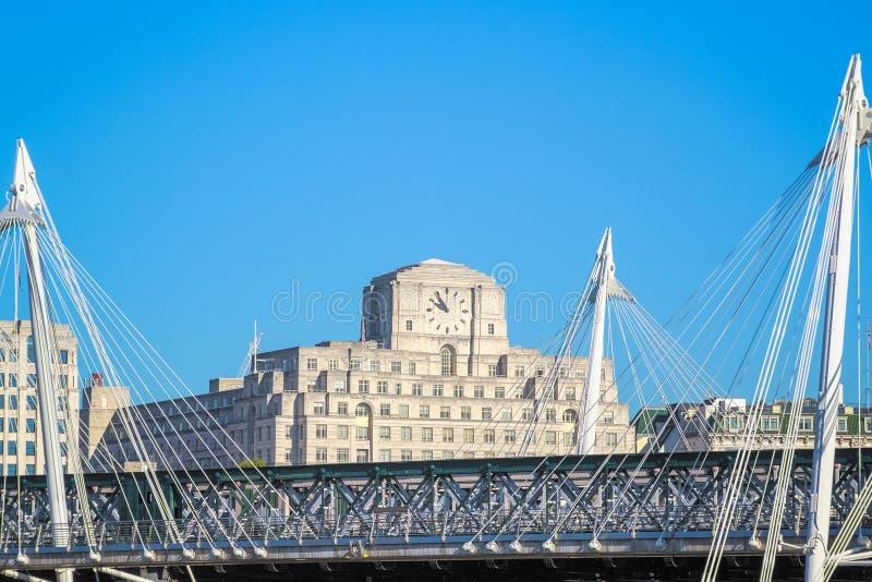 Puentes de oro del jubileo, una pasarela peatonal, con Shell Mex House en el fondo fotos de archivo libres de regalías