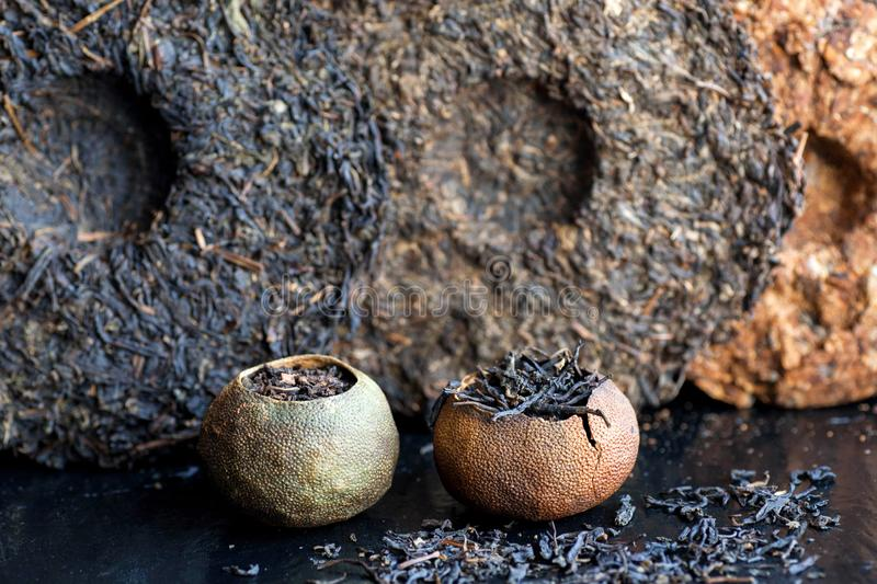 Puer raw tea. Pu-erh in different sorts and shapes. Tea cakes texture and orange tea made in traditional chinese way stock photos