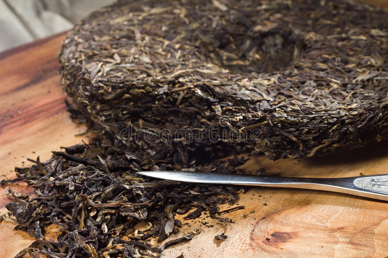 Puer tea cake and a puer knife. Breaking puer tea cake with special puer tea knife stock photography