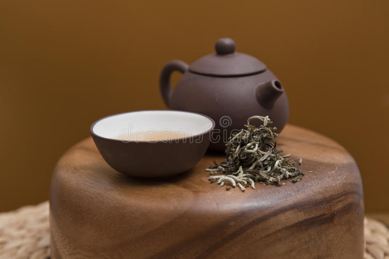 Puer tea. In a ceramic bowl and a ceramic teapot on a wooden bowl with mat royalty free stock photo