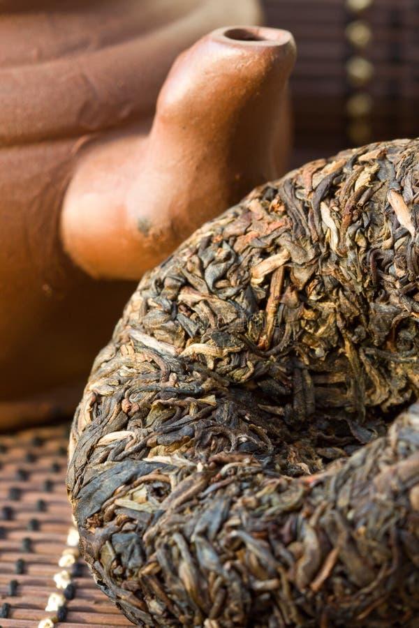 Puer tea. Disc Puer tea and ceramic teapot stock image