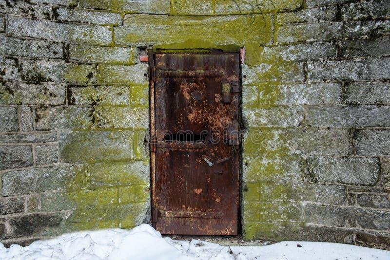 Puerta abandonada vieja del metal con moho en pared del castillo imagen de archivo libre de regalías