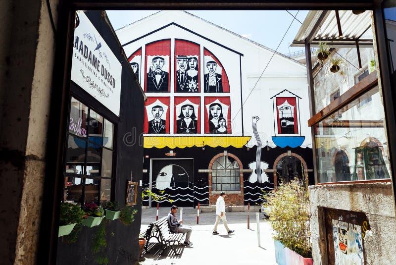 Puerta abierta al área urbana de la ciudad con la gente de relajación y algunas tiendas y cafés de moda foto de archivo