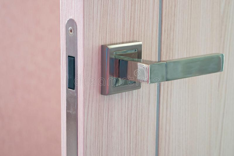 Puerta abierta en casa moderna Puerta de madera moderna con el detalle del primer de la manija del metal Fotografía del producto  fotografía de archivo