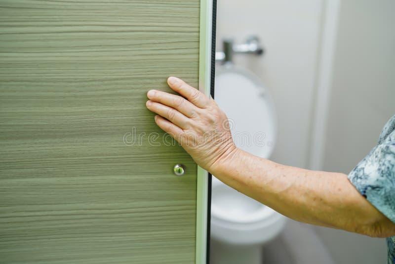 Puerta abierta paciente de la diapositiva del cuarto de ba?o del retrete de la mujer mayor mayor asi?tica de la se?ora mayor a ma fotografía de archivo