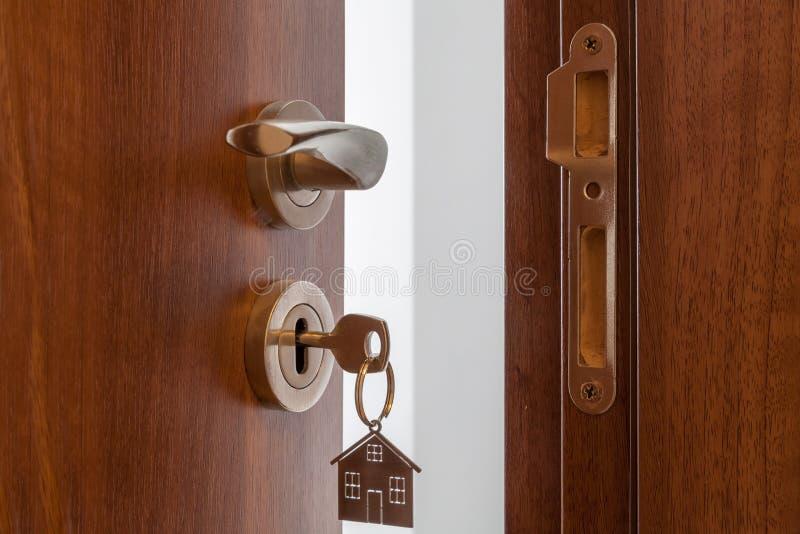 Puerta abierta a un nuevo hogar Tirador de puerta con llave y llavero formado hogar Hipoteca, inversión, propiedades inmobiliaria imágenes de archivo libres de regalías