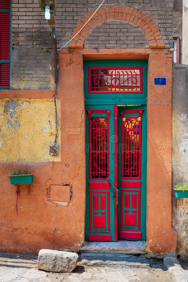 Puerta adornada viejo grunge pintada en colores vibrantes verdes y rojos en la pared de piedra pintada naranja fotos de archivo libres de regalías