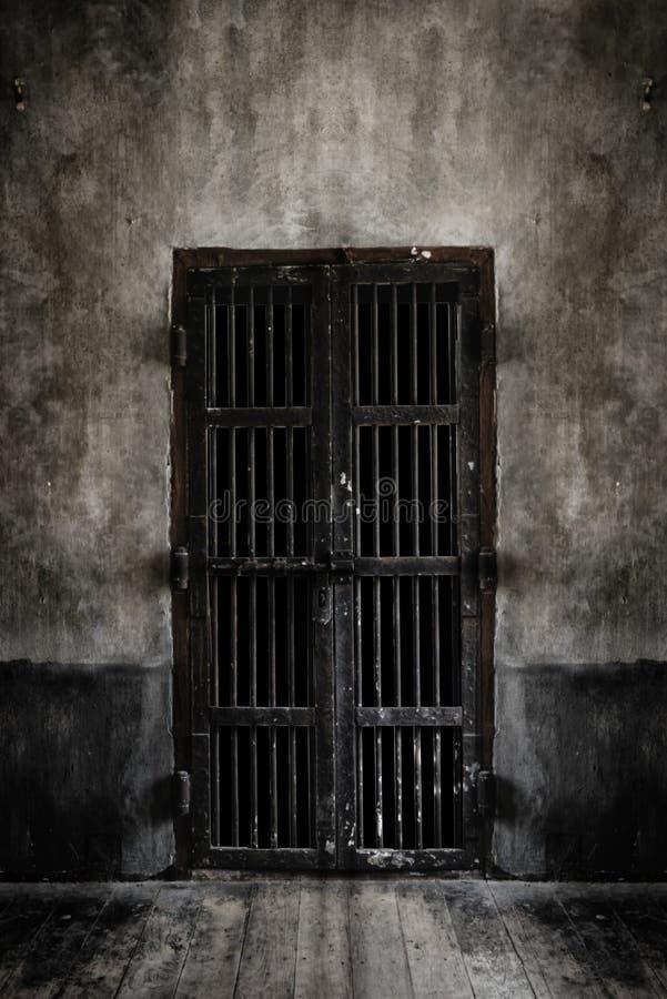 Puerta aherrumbrada de las barras de hierro en la pared vieja foto de archivo