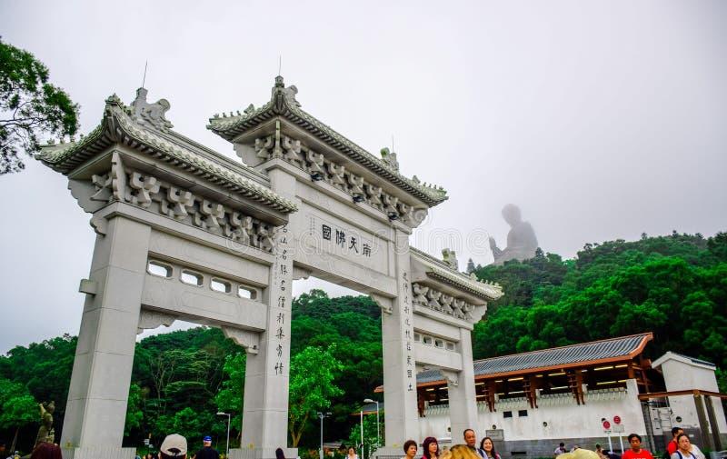 Puerta al Po Lin Monastery con la estatua de Tian Tan Buddha para arriba en la colina en Ngong Ping Village, Lantau Islan imagen de archivo