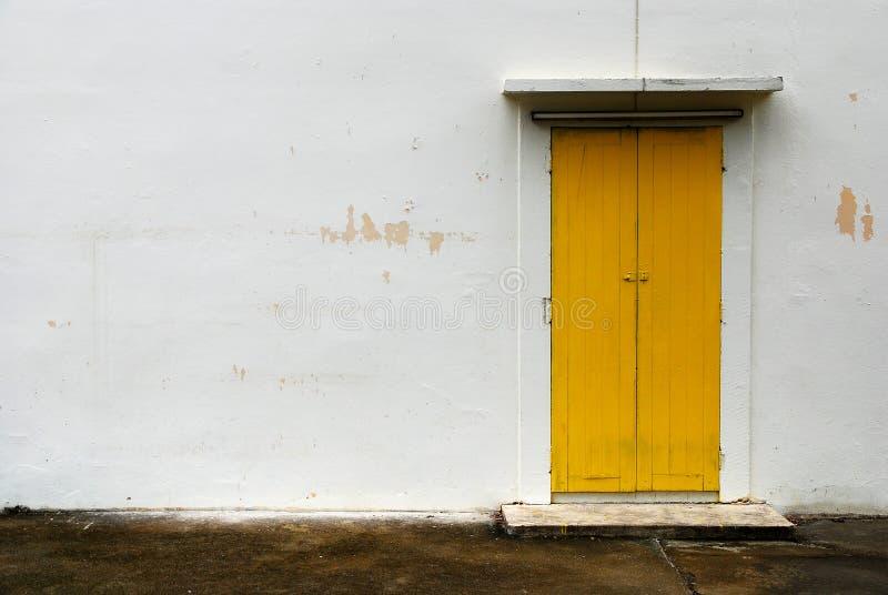Puerta amarilla en la pared blanca imagenes de archivo