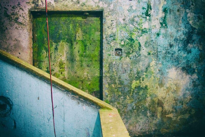 Puerta amarilla gastada y paredes azules en un edificio condenado Ningunas personas imágenes de archivo libres de regalías