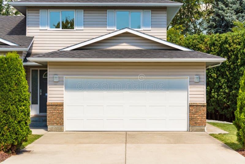Puerta ancha blanca del garaje de la casa residencial con la calzada concreta en frente imágenes de archivo libres de regalías