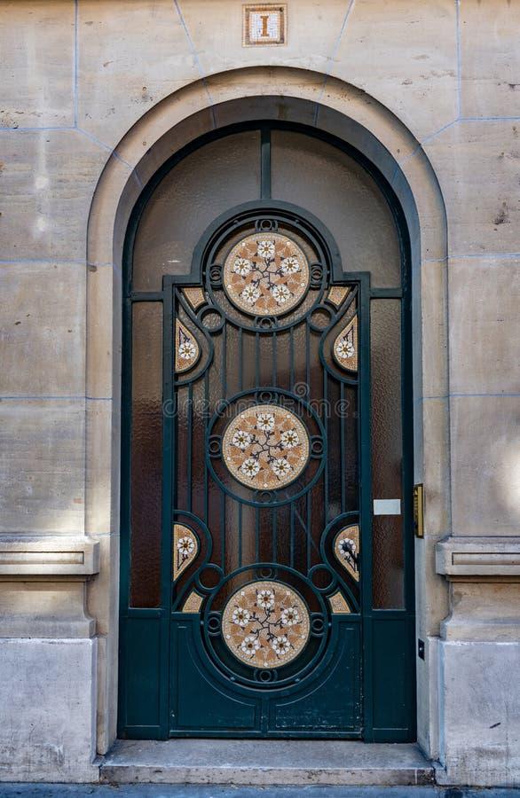 Puerta antigua del arco con los rosetones del mosaico y la pared de piedra del bloque del edificio viejo en París Francia Metal d fotos de archivo libres de regalías