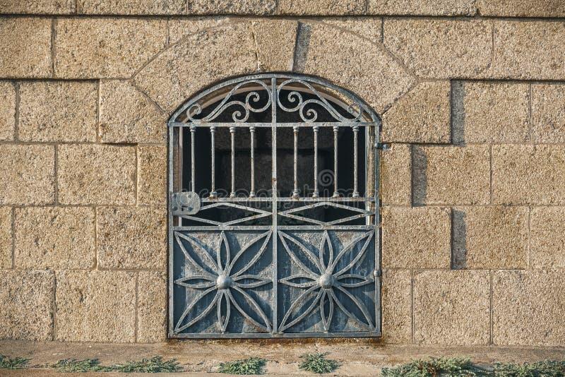 Puerta antigua del hierro con la pared marrón en ladrillos grandes imagenes de archivo