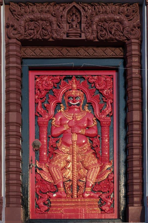 Puerta antigua roja con el encargado de puerta en LAK Mueang de Prachuap Khiri Khan fotografía de archivo