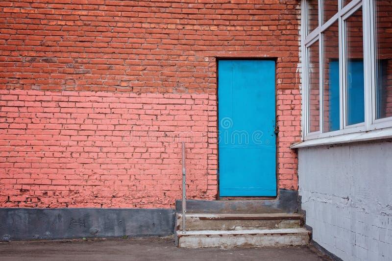 Puerta azul con pasos en la pared de ladrillo imágenes de archivo libres de regalías