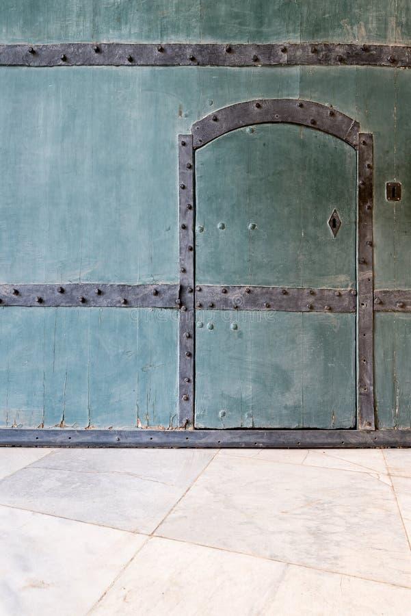 Puerta azul de madera cerrada en una pared azul de madera y un piso de mármol tejado fotos de archivo