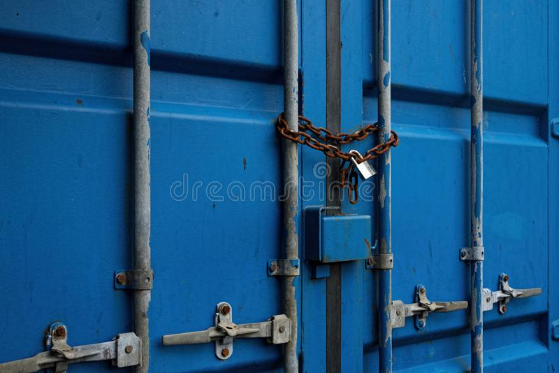Puerta azul del envase con Rusty Chain y el candado cerrado imágenes de archivo libres de regalías