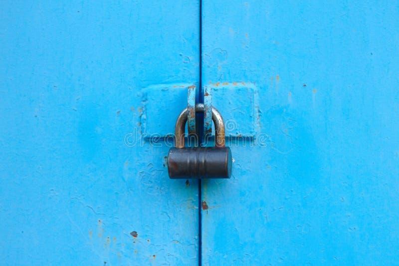 puerta azul del metal con el candado Viejas puertas del garaje con el ojo de la cerradura imagen de archivo