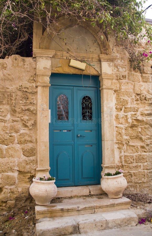Puerta azul del metal en casa vieja foto de archivo