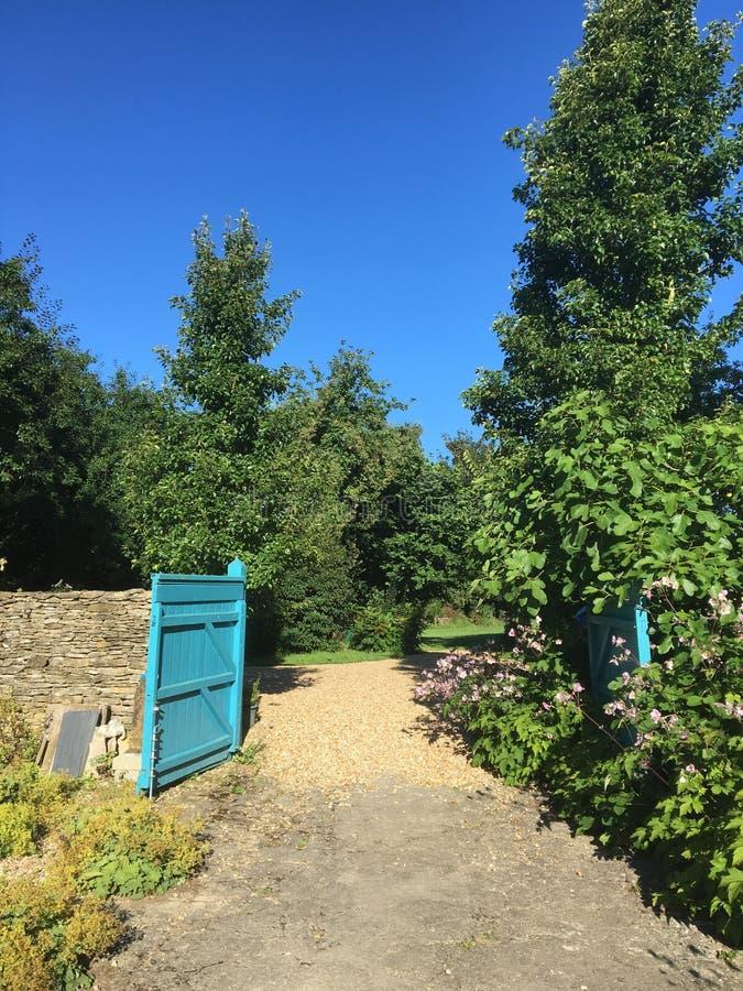 Puerta azul en el camino de la grava fotos de archivo libres de regalías