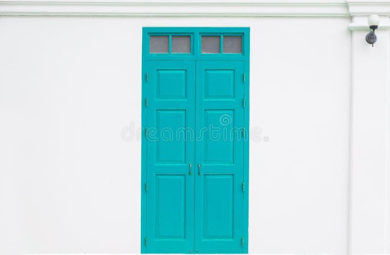 Puerta azul tradicional de madera de un viejo en la pared blanca imágenes de archivo libres de regalías