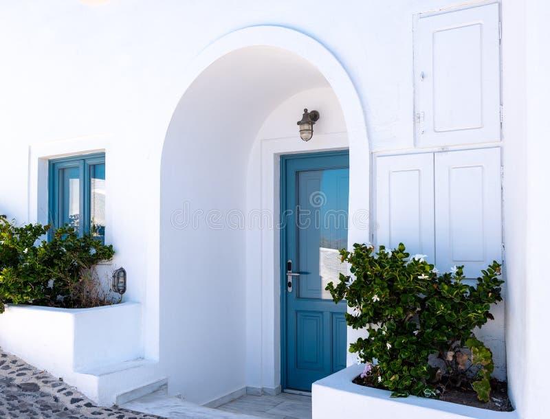 Puerta azul y ventana azul en casa griega blanca tradicional en la isla de Santorini, Grecia imagen de archivo