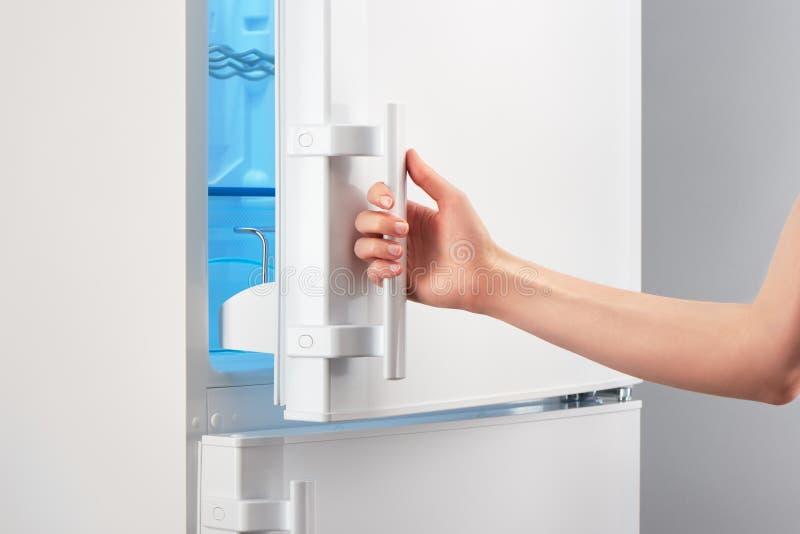 Puerta blanca de apertura del refrigerador de la mano femenina en gris fotografía de archivo