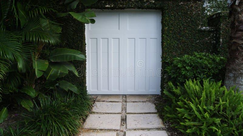 Puerta blanca de la puerta a un jardín tropical fotografía de archivo libre de regalías
