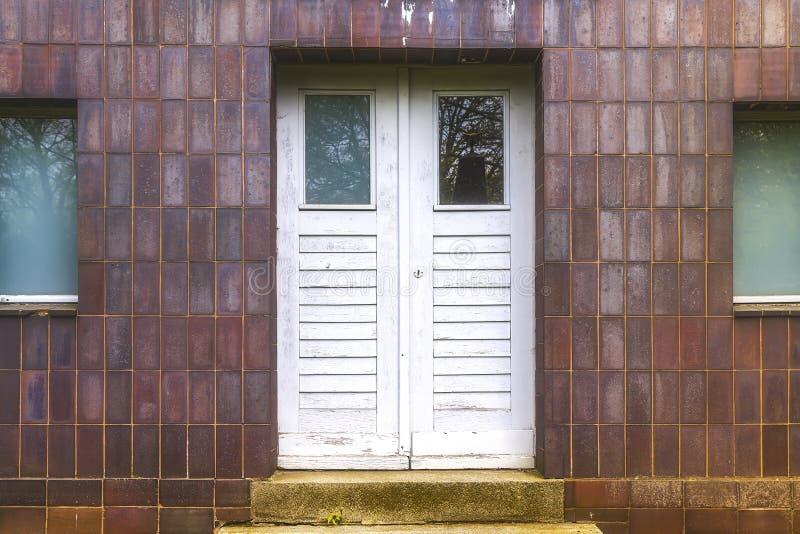 Puerta blanca vieja y pared tieled rojo imagen de archivo libre de regalías
