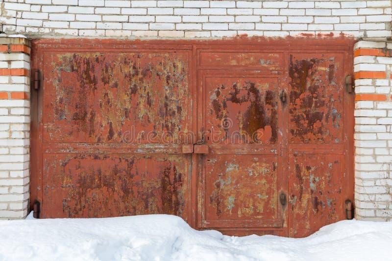 Puerta cerrada del garaje del hierro con las marcas del moho imagen de archivo