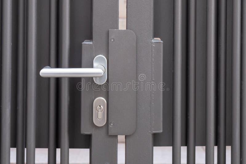 Puerta cerrada del hierro con el tirador de puerta fotografía de archivo