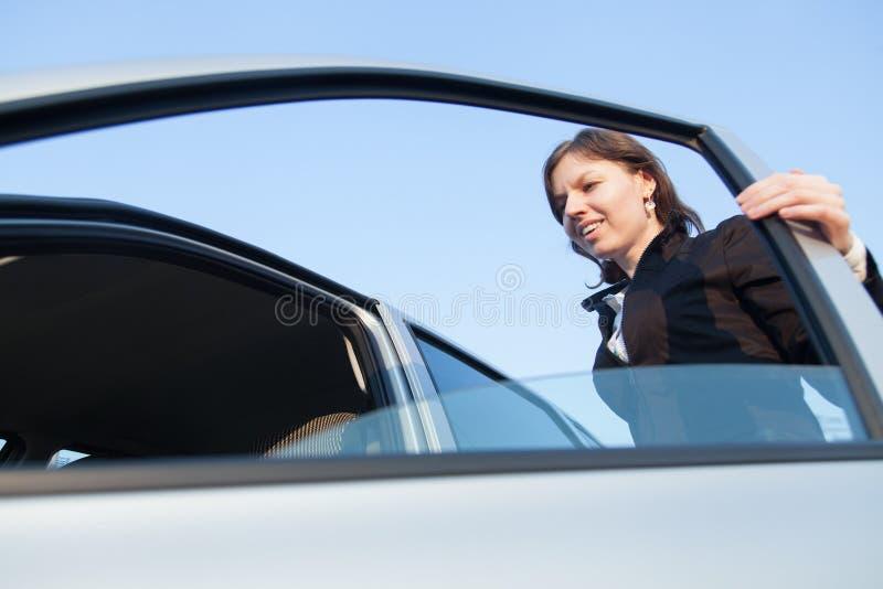 Puerta de abertura de la mujer de su coche imagen de archivo