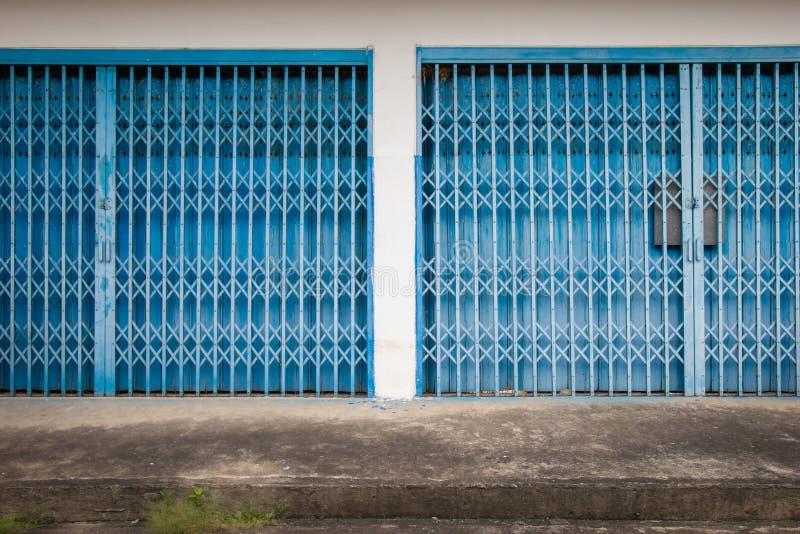 Puerta de acero azul vieja con los pisos concretos viejos Puerta de acero vieja foto de archivo