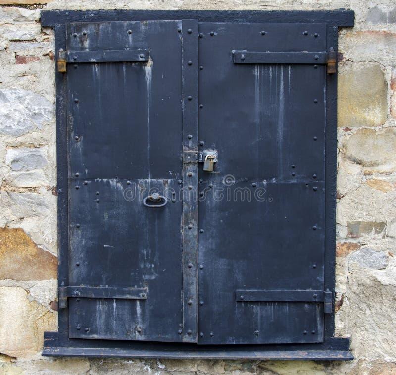 Puerta de acero en un edificio de piedra imagen de archivo