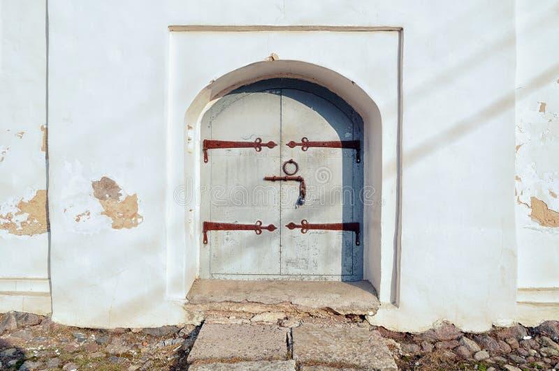 Puerta de acero envejecida con los henges y las manijas oxidados de la puerta imagen de archivo libre de regalías