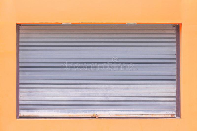 Puerta de acero rodante gris o puerta del obturador del rodillo con el candado en el fondo anaranjado de la pared, modelos del me imagen de archivo