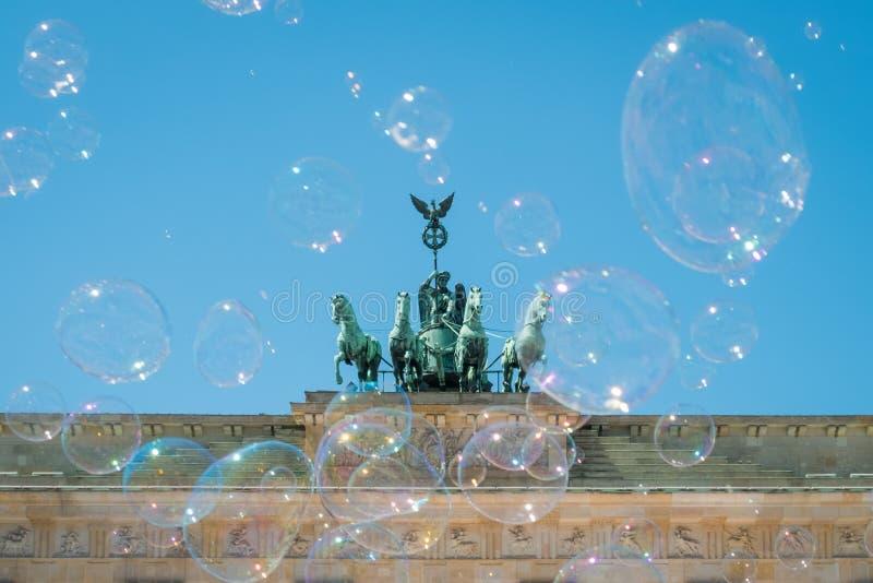 Puerta de Brandeburgo/Tor de Brandenburger el día soleado con las burbujas del cielo azul y de jabón imagen de archivo