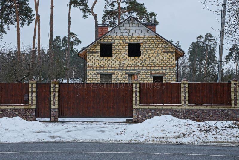 Puerta de Brown y cerca de madera delante de un hogar inacabado en la carretera de asfalto en la nieve fotos de archivo libres de regalías
