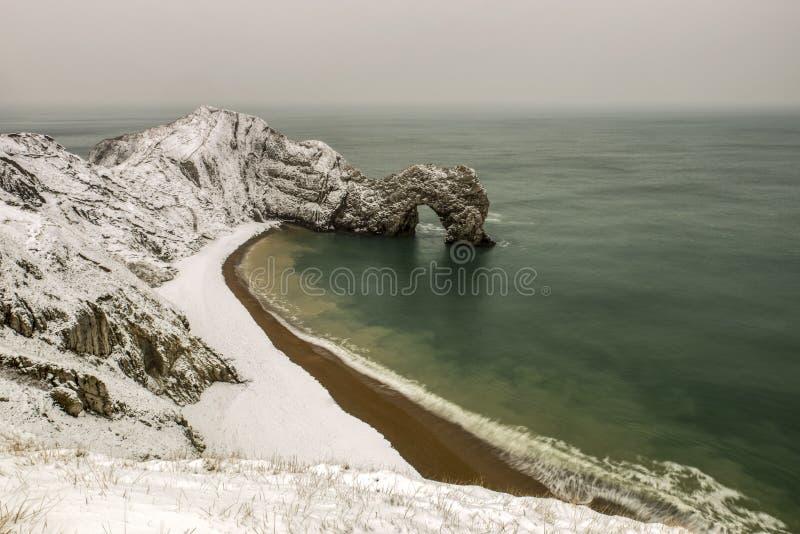 Puerta de Durdle cubierta en nieve en una mañana del invierno imágenes de archivo libres de regalías