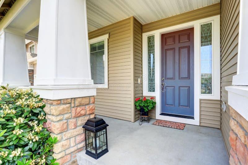 Puerta de entrada delantera con el pórtico del piso y el pote de flores concretos imagen de archivo