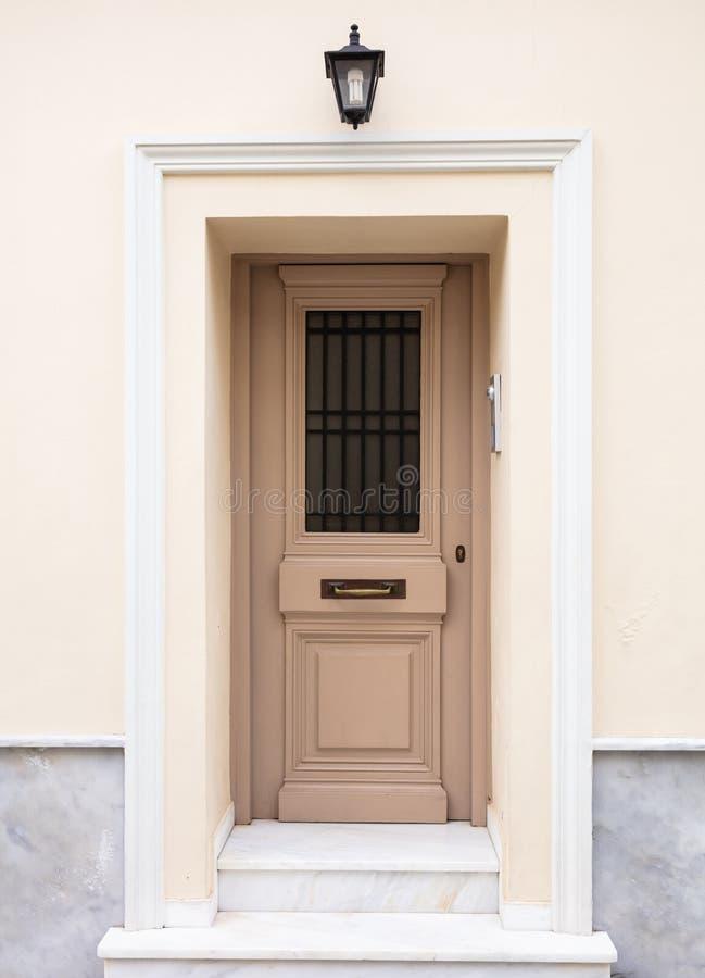 Puerta de entrada de madera, fondo beige de la pared del color, edificio residencial en la ciudad vieja de Plaka, Atenas Grecia imagenes de archivo