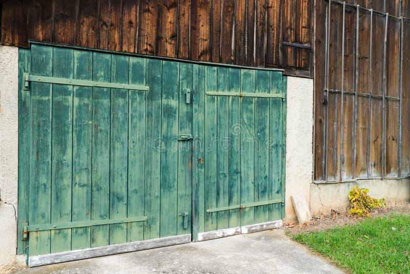 Puerta de granero de madera verde rústica del viejo vintage en una vertiente de madera foto de archivo