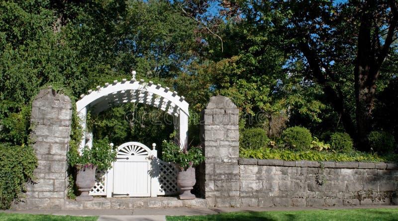 Puerta de jardín con la pared de piedra fotografía de archivo