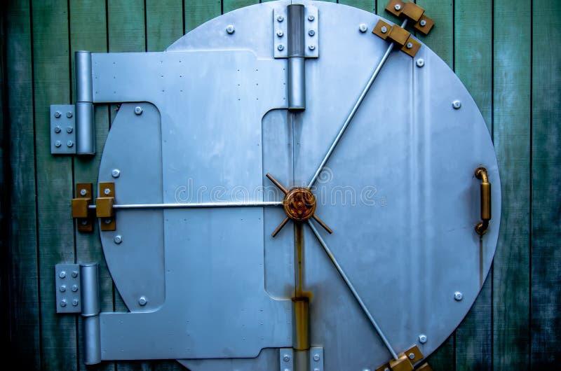 Puerta de la cámara acorazada de la seguridad en la pared verde foto de archivo