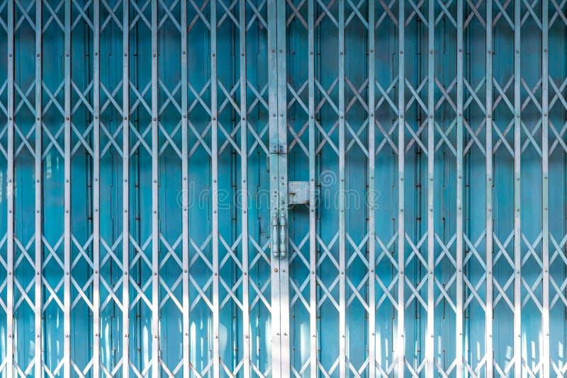 Puerta de la casa de metal plegable, metal antiguo, puerta de hierro Puerta de acero al aire libre estirado azul en el exterior c foto de archivo