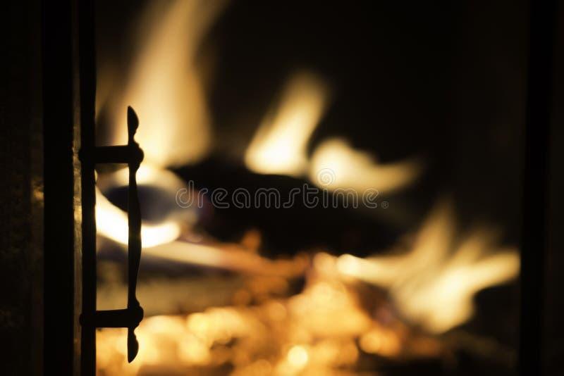 Puerta de la chimenea en silueta con el fuego ardiente en fondo fotografía de archivo