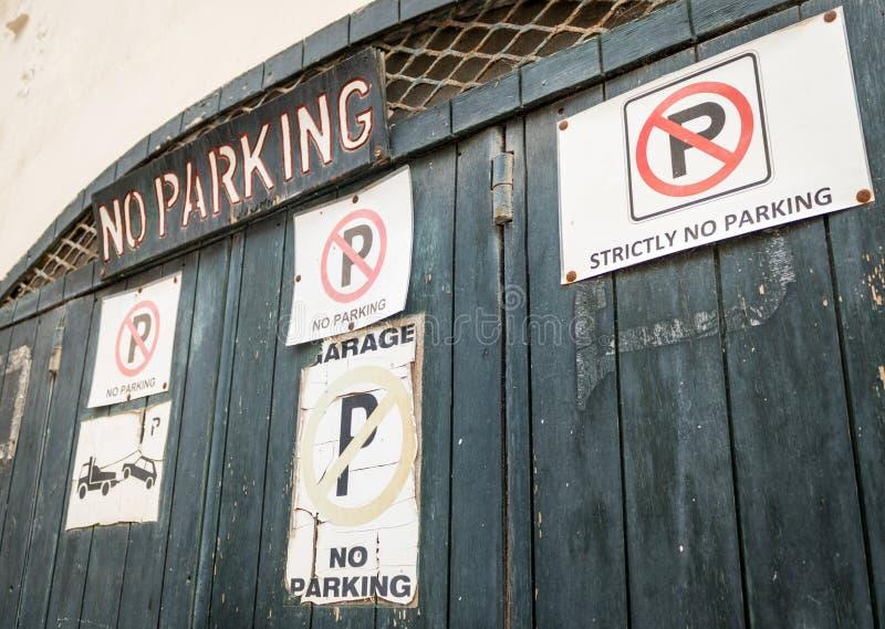 Puerta de la entrada con muchas diversos muestras y poner letras del estacionamiento prohibido fotografía de archivo